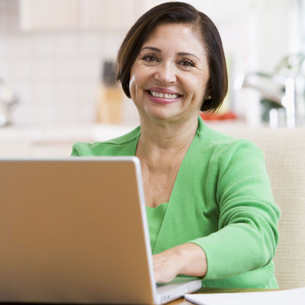 An middle-aged woman smiling while typing on her laptop.